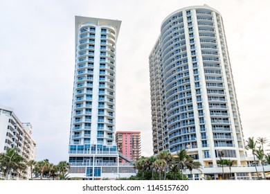 Sunny Isles Beach, USA - May 7, 2018: Oceanfront Park, buildings along coast in Miami, Florida evening, green palm trees, nobody looking up at skyscrapers