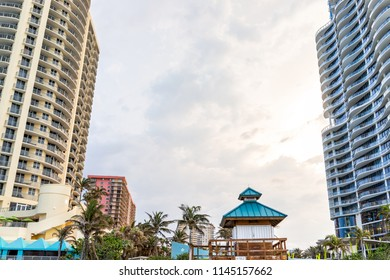 Sunny Isles Beach, USA - May 7, 2018: Gilbert Samson Oceanfront Park, building along coast in Miami, Florida evening, green palm trees, nobody looking up at skyscrapers, Winston Towers