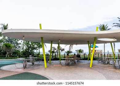 Sunny Isles Beach, USA - May 7, 2018: Gilbert Samson Oceanfront Park, building along coast in Miami, Florida evening, people sitting on picnic tables under roof, green palm trees
