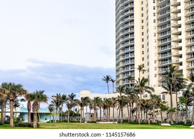 Sunny Isles Beach, USA - May 7, 2018: Gilbert Samson Oceanfront Park, apartment condo hotel skyscraper building balconies along coast in Miami, Florida evening, people walking, green palm trees