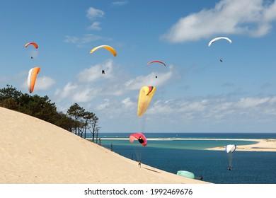 Dans un paysage ensoleillé avec un ciel bleu parsemé de nuages, de nombreux parapentistes se sont rassemblés pour voler sur la dune de Pyla