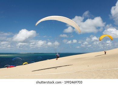 Dans un paysage ensoleillé avec un ciel bleu parsemé de nuages, un parapente décolle de la dune pyla