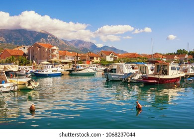 Sunny landscape with fishing boats in harbor. Montenegro, Marina Kalimanj in Tivat city