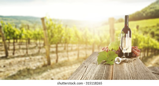 sunny landscape of vineyard with green leaves and gray wooden table of wine bottle