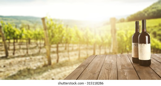 sunny landscape of vineyard with green leaves and bottles of wine on table
