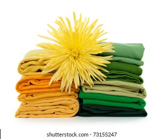 Sunny laundry. Flower on top of green and yellow clothes piles.