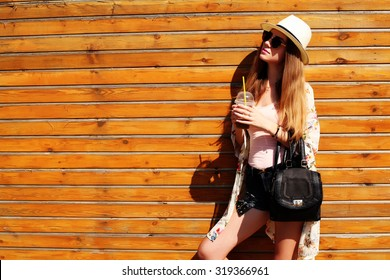 Sunny lifestyle fashion portrait of young stylish hipster woman walking on the street, wearing trendy outfit, hat, kimono, drinking tasty smoothie, travel with backpack. Wood background