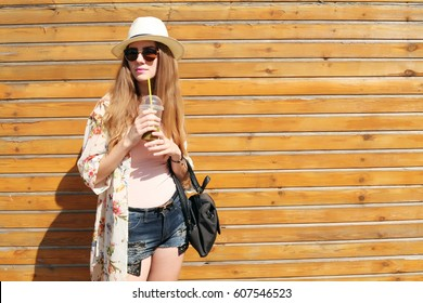 Sunny lifestyle fashion portrait of young stylish hipster woman walking on the street, wearing trendy outfit, kimono, drinking tasty smoothie, travel with backpack. Wood background