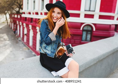 Sunny lifestyle portrait of cute cheerful young girl with amazing red hair  posing on the street, holding retro film camera, laughing.