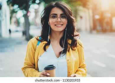 Sunny lifestyle portrait of young european woman walking in the city listening to music by smartphone, happy smiling stylish girl enjoying summer vacation in Europe, Lifestyle People Tourist