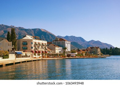 Sunny Mediterranean town at the foot of mountains. Montenegro, Bay of Kotor, view of embankment of Tivat city. Free space for text