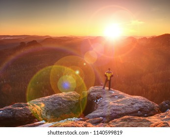 Sunny morning in amazing landscape. Happy hiker with raised arms stay alone on sharp rock above pine forest.