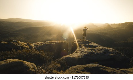 Sunny morning in amazing landscape. Happy hiker with raised arms stay alone on sharp rock above pine forest., Europe (Saechsische Schweiz)