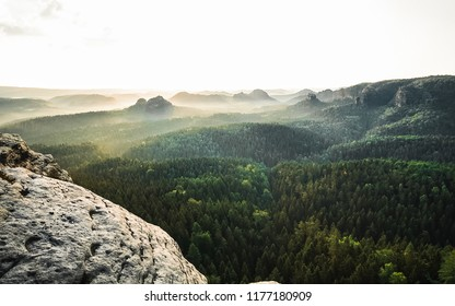 Sunny morning in amazing landscape. Happy hiker with a sleeping bag sitting alone on a sharp rock above the pine forest.