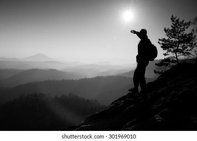 Sunny morning. Hiker is standing on the peak of rock in rock empires park and watching over the misty and foggy morning valley to Sun.