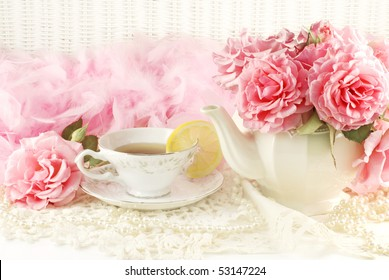 A sunny morning ladies breakfast tea with a teapot of fresh pink garden roses