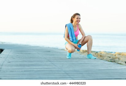 Sunny morning on the beach, athletic woman resting after running at the morning training by the sea