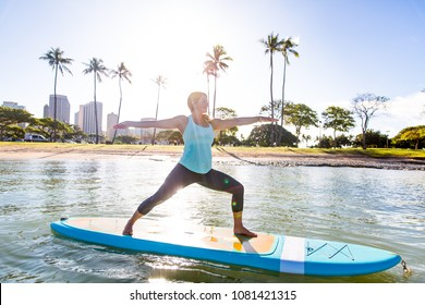 Sunny morning sun flare moment of a pretty young woman in SUP Yoga practice in warrior pose
