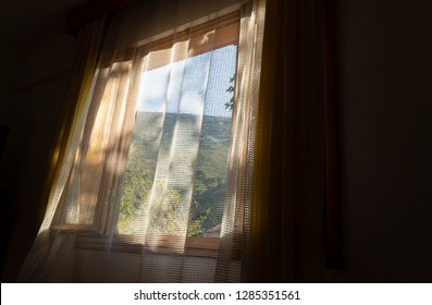In sunny morning, from window of a room, romantic mountain view behind the curtains