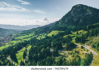 Sunny mountain landscape with curvy road in the German Allgau Alps with bright green colors