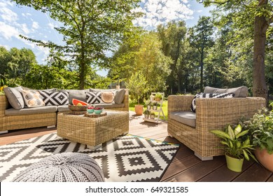 Sunny outdoor terrace with rattan furnitures in big garden