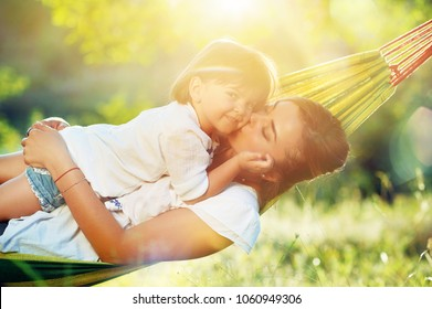 Sunny picture of a mother with daugther in a hammock