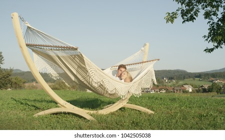 Sunny picturesque countryside surrounds lovely Caucasian couple cuddling in a hammock. Young man snuggles up to pretty blonde girl while swaying on fabric sling in the picturesque summer countryside.