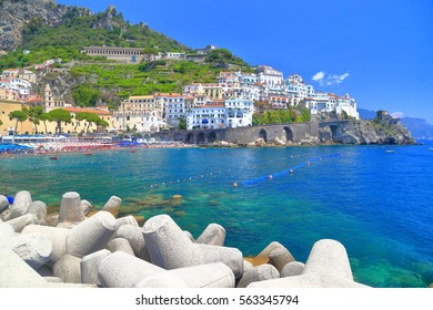 Sunny pier and traditional buildings in Amalfi village, Amalfi coast, Italy