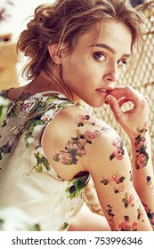 Sunny portrait of beautiful young sexy woman with light hair and flower tattoos on her arms and shoulders wearing silk floral dress in studio with plants and straw chair