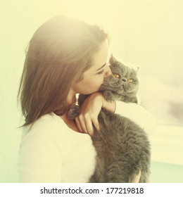 Sunny portrait of a girl who kisses a cat