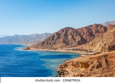 Sunny resort beach at the coast shore of Red Sea in Dahab, Sinai, Egypt, Asia in summer hot. Famous tourist destination Blue Hole near of Sharm el Sheikh. Bright sunny light