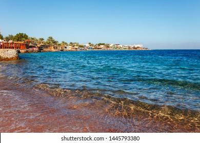 Sunny resort beach at the coast shore of Red Sea in Dahab, Sinai, Egypt, Asia in summer hot. Famous tourist destination near of Sharm el Sheikh. Bright sunny light