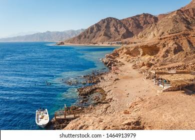 Sunny resort beach at the coast shore of Red Sea in Dahab, Sinai, Egypt, Asia in summer hot. Famous tourist destination Blue Hole near of Sharm el Sheikh. Bright sunny light