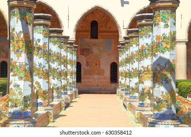 Sunny rows of beautiful pillars plated with majolica tiles at the cloister of the Clarisses inside Santa Chiara Monastery in Naples, Italy