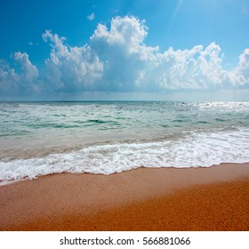 sunny sandy beach of the Mediterranean Sea under the blue summer sky with clouds