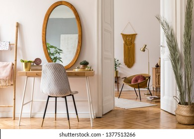 Sunny scanidnavian interiors of apartment with big mirror, dressing table, gold armchair, design accessories and furnitures, plants, palm leaves, yellow macrame. Stylish home decor of rooms.