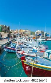 Sunny Scene of Fishing Boats and Heraklion Promenade, Crete, Greece