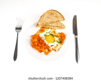 Sunny side up egg on plate with fried tomatoe and bread sandwich, with knife and fork over bright background at breakfast