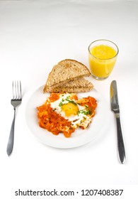 Sunny side up egg on plate with fried tomato and toasted bread sandwich, with knife and fork over bright background at breakfast