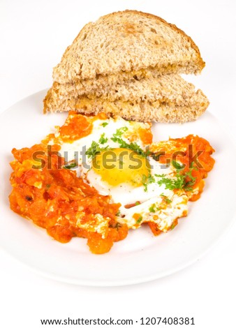 Sunny side up egg on plate with fried tomato and toasted bread sandwich, over bright background at breakfast