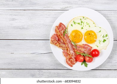 Sunny Side Up Eggs with crispy fried bacon, arugula and tomatoes on white plate on wooden table, view from above