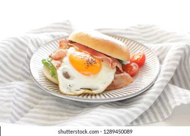 Sunny side up fried egg and bacon sandwich