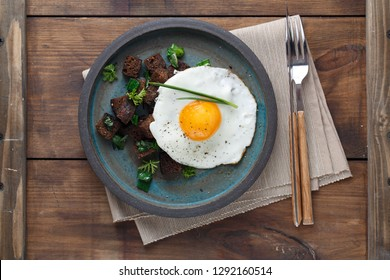 Sunny side fried egg with croutons and herbs, close view