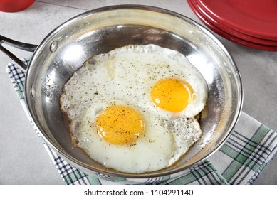 Sunny side up fried eggs in a stainless steel frying pan