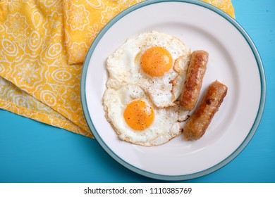sunny side up organic eggs with breakfast sausages, a ketogenic diet meal