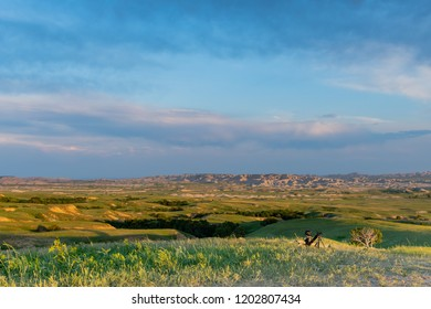Sunny Skies Over Badlands and Grassy Fields with Slider