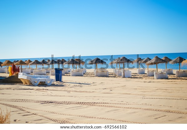 Sunny sky and chairs with parasol on the beautiful sandy beach of Portugal