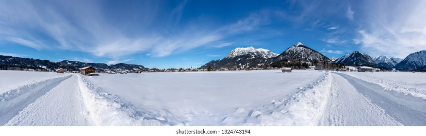 Sunny snow covered landscape near Oberstdorf, Bavaria, Germany. Panorama with hiking trail.