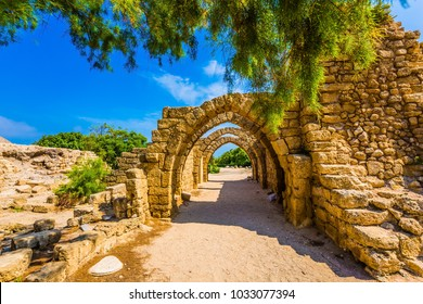 Sunny spring day. Arched passage - covered street. Picturesque ruins of the ancient seaport Caesarea. Israel. Concept of ecological and historical tourism