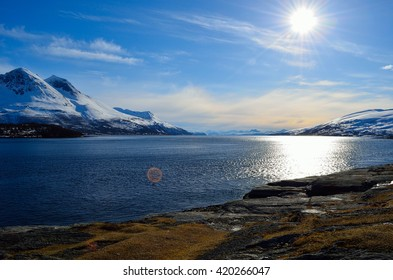 Sunny spring day with mighty snow covered mountain and ocean in the front in Hella, Norway